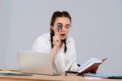 Jeune belle femme d'affaires s'asseyant sur le lieu de travail, tenant le livre et la loupe Image stock