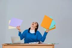 Jeune belle femme d'affaires s'asseyant sur le lieu de travail, tenant les dossiers colorés Photos stock