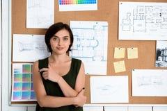 Jeune belle femme d'affaires souriant, bureau proche debout avec des dessins Fond de bureau Photo libre de droits