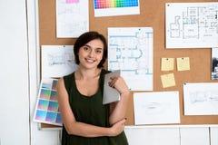 Jeune belle femme d'affaires souriant, bureau proche debout avec des dessins Fond de bureau Photographie stock