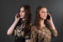 jeune belle femme d'affaires sur un fond d'isolement Deux amies parlant au téléphone Image libre de droits