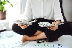 Jeune belle femme d'affaires tenant l'argent, se reposant sur la table sur le lieu de travail Images stock