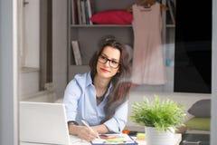 Jeune belle femme d'affaires travaillant à la maison photographie stock