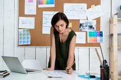 Jeune belle femme d'affaires travaillant avec des dessins sur le lieu de travail Fond de bureau Images libres de droits