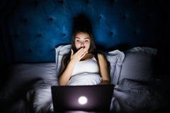 Jeune belle femme d'intoxiqué d'Internet dans des pyjamas sur le fonctionnement de chambre à coucher de lit à la maison ennuyé et photographie stock libre de droits