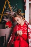 Jeune belle femme dans des pyjamas chauds rouges avec les ornements scandinaves se reposant près de la cheminée décorative et du  Image stock