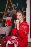 Jeune belle femme dans des pyjamas chauds rouges avec les ornements scandinaves se reposant près de la cheminée décorative et du  Photo stock