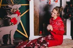 Jeune belle femme dans des pyjamas chauds rouges avec les ornements scandinaves se reposant près de la cheminée décorative et du  Images libres de droits
