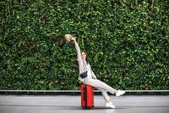 Jeune belle femme dans l'aéroport contre le mur vert photographie stock libre de droits