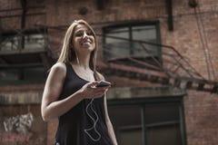 Jeune belle femme dans la musique de écoute de ville Photographie stock