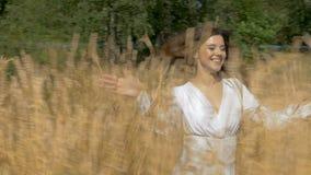 Jeune belle femme dans la robe blanche fonctionnant à travers le champ avec du blé banque de vidéos