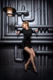 Jeune, belle femme dans la robe noire tenant deux rétros lampes Photos stock