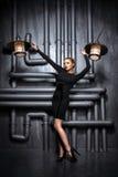 Jeune, belle femme dans la robe noire tenant deux rétros lampes Photographie stock libre de droits