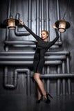 Jeune, belle femme dans la robe noire tenant deux rétros lampes Photo libre de droits