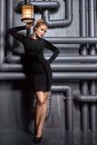 Jeune, belle femme dans la robe noire tenant deux rétros lampes Photographie stock