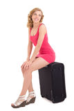 Jeune belle femme dans la robe rose se reposant sur la grande valise plus de Photographie stock libre de droits