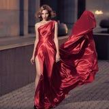 Jeune belle femme dans la robe rouge de flottement Fond de ville Images libres de droits