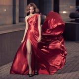 Jeune belle femme dans la robe rouge de flottement Fond de ville Image stock