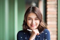 Jeune belle femme dans le café près de la fenêtre, pensant et écrivant quelque chose Image stock