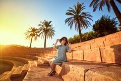 Jeune belle femme dans le chapeau de plage se reposant sur les étapes d'un amphithéâtre antique au jour ensoleillé dans Bodrum, T photos stock