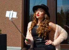 Jeune belle femme dans le chapeau faisant le selfie dehors Instagram PO Photos libres de droits