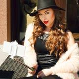 Jeune belle femme dans le chapeau faisant le selfie dehors Technologie c Image stock