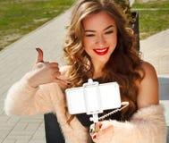 Jeune belle femme dans le chapeau faisant le selfie montrant dehors l'appel Photos libres de droits