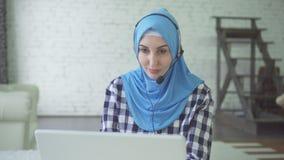 Jeune belle femme dans le hijab avec les écouteurs et le casque, travailleur de centre de calorie images stock