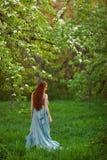 Jeune belle femme dans le jardin de floraison Photographie stock libre de droits