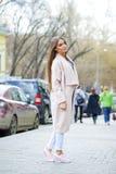Jeune belle femme dans le manteau beige et le snea de jean et rose déchiré Photographie stock