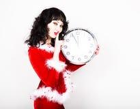 Jeune belle femme dans le manteau rouge tenant la grande horloge blanc au moment de l'exécution d'isolement par concept de fond Photos libres de droits