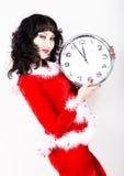 Jeune belle femme dans le manteau rouge tenant la grande horloge blanc au moment de l'exécution d'isolement par concept de fond Images stock