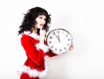Jeune belle femme dans le manteau rouge tenant la grande horloge blanc au moment de l'exécution d'isolement par concept de fond Image libre de droits