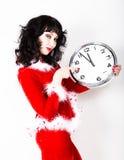 Jeune belle femme dans le manteau rouge tenant la grande horloge blanc au moment de l'exécution d'isolement par concept de fond Photographie stock