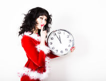 Jeune belle femme dans le manteau rouge tenant la grande horloge blanc au moment de l'exécution d'isolement par concept de fond Photos stock
