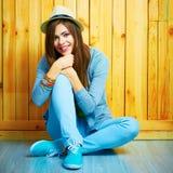 Jeune belle femme dans le style de la jeunesse de hippie se reposant sur un floo photographie stock libre de droits
