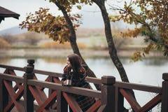 Jeune belle femme dans un thé potable de manteau classique chaud près de lac Image libre de droits
