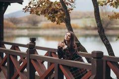 Jeune belle femme dans un thé potable de manteau classique chaud près de lac Images libres de droits