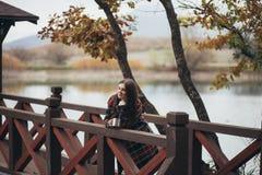 Jeune belle femme dans un thé potable de manteau classique chaud près de lac Photos stock