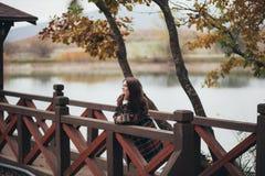 Jeune belle femme dans un thé potable de manteau classique chaud près de lac Photographie stock