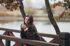 Jeune belle femme dans un thé potable de manteau classique chaud près de lac Images stock