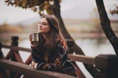 Jeune belle femme dans un thé potable de manteau classique chaud près de lac Photo libre de droits