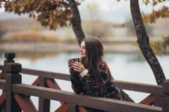Jeune belle femme dans un thé potable de manteau classique chaud près de lac Photo stock