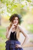 Jeune belle femme dans une guirlande des fleurs dehors Image libre de droits