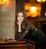 Jeune belle femme de brune dans la robe noire élégante se tenant près d'un piano de vintage Dame romantique sensuelle avec de lon Images libres de droits