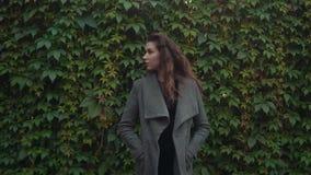 Jeune belle femme de brune dans le manteau souriant dans le mouvement lent avec l'espace de copie banque de vidéos