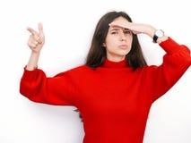 Jeune belle femme de brune dans regarder de pensée de chandail rouge au côté l'espace vide de copie, d'isolement au-dessus du fon Photos stock