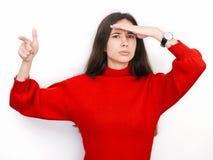 Jeune belle femme de brune dans regarder de pensée de chandail rouge au côté l'espace vide de copie, d'isolement au-dessus du fon Photographie stock libre de droits