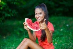 Jeune belle femme de brune mangeant la pastèque Image libre de droits