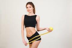 Jeune belle femme de brune mesurant sa taille avec une bande de mesure sur le fond blanc photos libres de droits